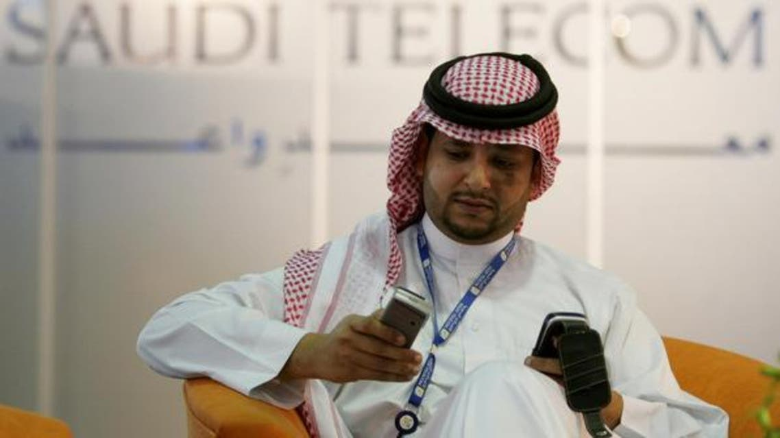 A Saudi man looks at his mobile phone in front of a Saudi Telecom sign in Riyadh April 25, 2005. (File: Reuters)