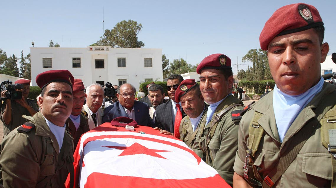 Tunisia's President Moncef Marzouki, center, helps carrying the coffin of a soldier during a ceremony in Kasserine, Tunisia, Tuesday, July, 30, 2013.