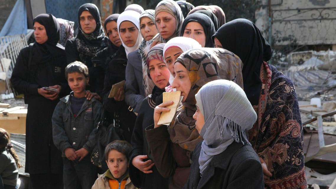 People wait to collect food aid distributed by UNRWA at the Yarmouk refugee camp. (Reuters)