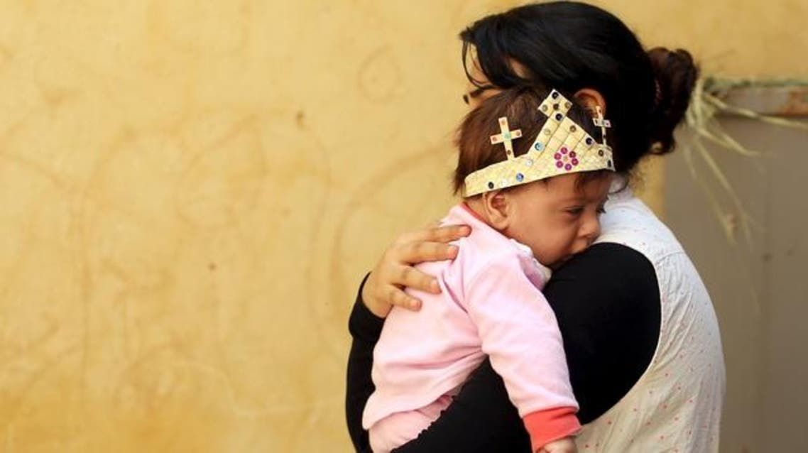An Egyptian Coptic Christian carries her baby who wears a palm decoration during Palm Sunday inside a church in Old Cairo, April 5, 2015. (Reuters)