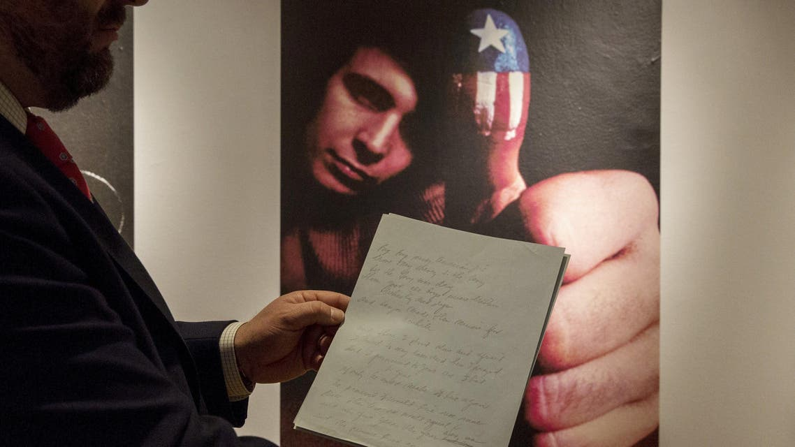 """Christie's curator Tom Lecky holds the original manuscript for singer Don McLean's """"American Pie"""" at Christie's auction house in New York April 2, 2015. The original manuscript, which contains the lyrics to the iconic song written between 1970 and 1971 will be auctioned off in New York on April 7. REUTERS/Brendan McDermid"""