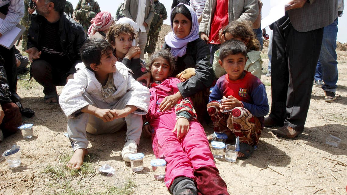 Members of the Yazidi minority sect who were newly released wait along a road on the outskirts of Kirkuk April 8, 2015. (Reuters)