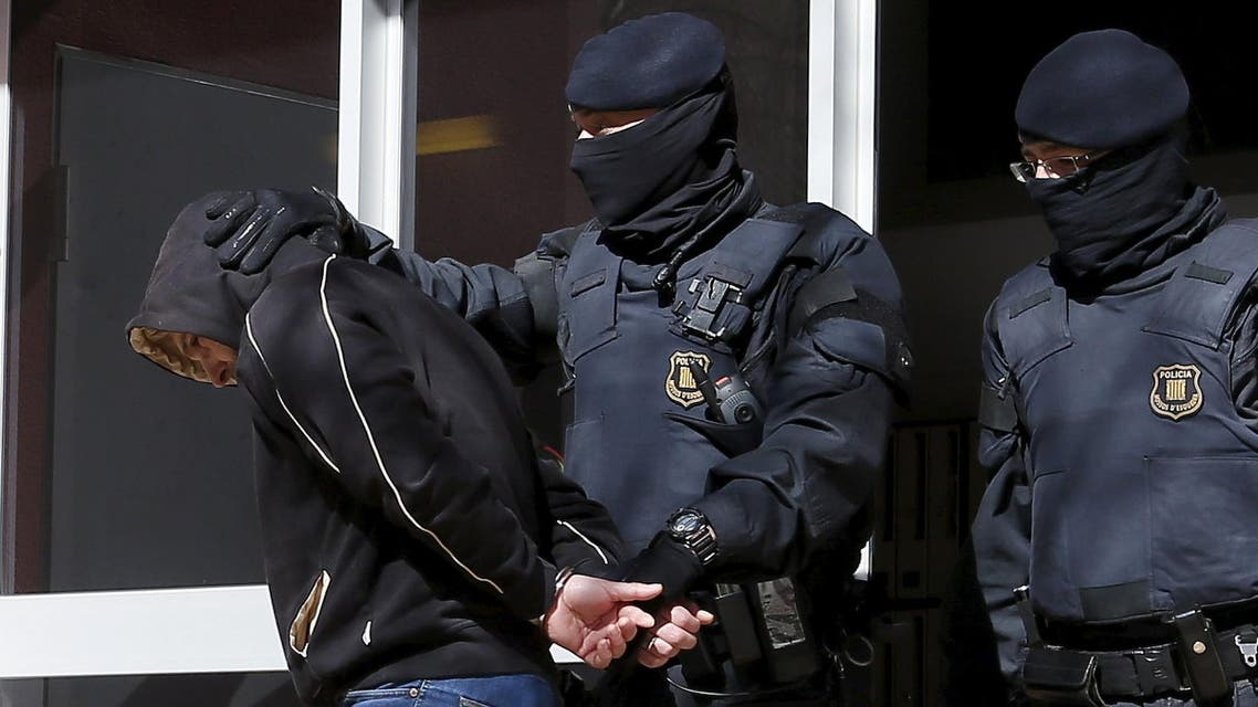 Catalan police escort a detained suspect from a block of flats during an operation against Islamist militants in Sabadell, April 8, 2015 (Reuters)