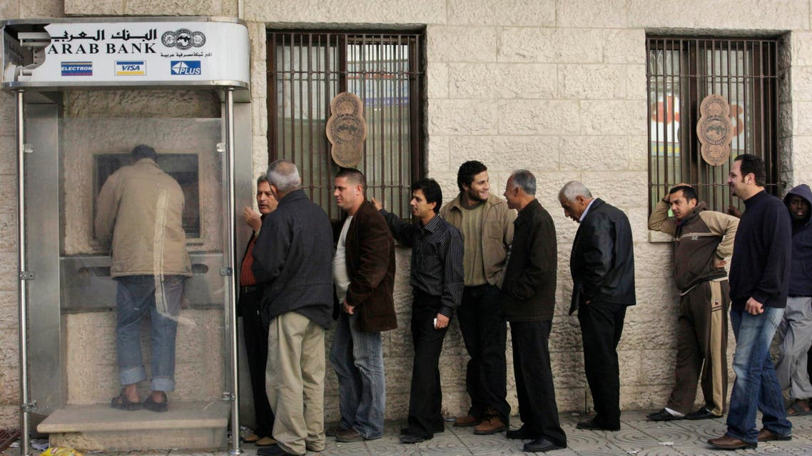 Palestinians wait to take money from a bank machine at an Arab Bank branch in Gaza City, Friday, Dec. 12, 2008. (File: AP)