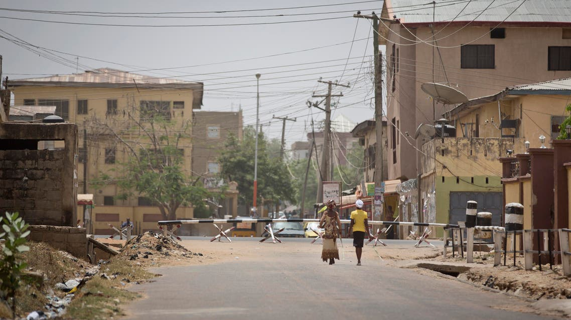 Two women walk down a deserted street with roadblocks at the end leading to the St Charles Catholic Church, scene of a 2014 bomb attack blamed on Boko Haram Islamic insurgents, in the mainly Christian Sabon Gari neighborhood of Kano, northern Nigeria on Palm Sunday, March 29, 2015. Normally the church would be packed with up to four masses on Palm Sunday, but this year it held only one which was half-full, due to large numbers of Christians leaving before the elections, fearing violence and retribution after election results will be announced in the predominantly Muslim town. (AP Photo/Ben Curtis)