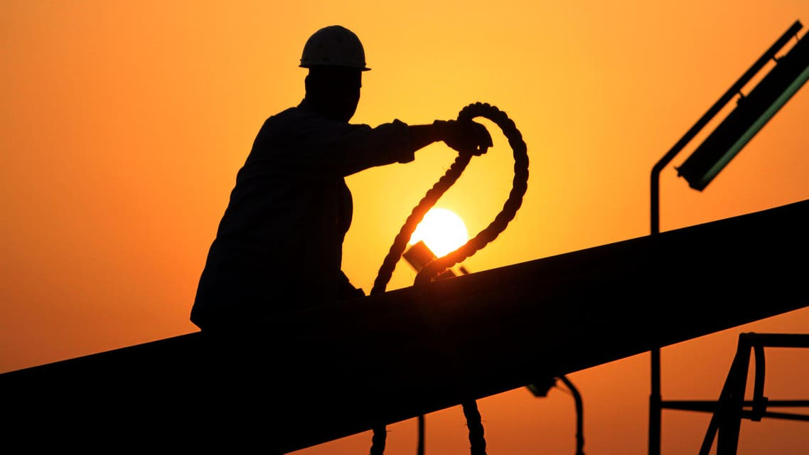 An unidentified oilfield worker ties pipes to be raised on an oil rig as the sun sets Wednesday, July 7, 2010, in the Persian Gulf desert oil field of Sakhir, Bahrain.(File photo: AP)