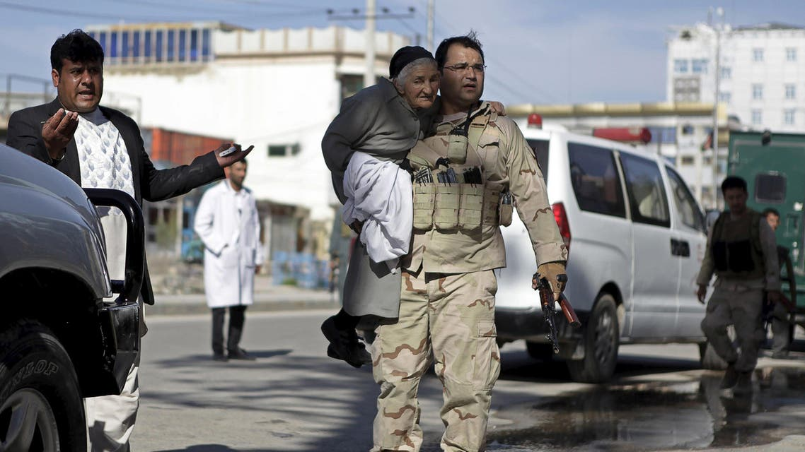 A member of the Afghan security force holds a woman while rescuing her from the site of an attack in Mazar-i-Sharif, April 9, 2015. (Reuters)