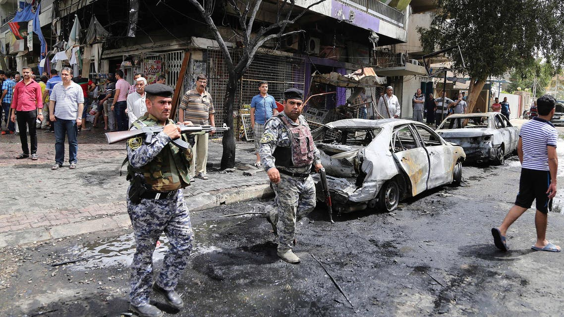 People and security forces gather at the site of a car bomb explosion at a convenience store in the Karrada neighborhood of Baghdad, Iraq, Friday, April 10, 2015. Iraqi officials say the blast in the downtown district killed several people and wounded a dozen. (AP Photo/ Karim Kadim)