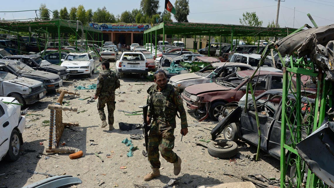 Afghan security personnel walk through the site of a suicide car bomb attack targeting a NATO convoy near the airport in Jalalabad on April 10, 2015.  (AFP)
