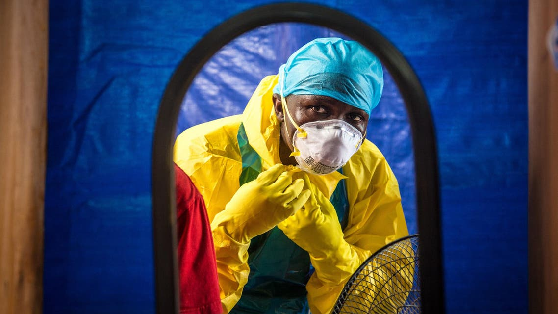 In this Thursday, Oct. 16, 2014 file photo, a healthcare worker dons in protective gear before entering an Ebola treatment center in the west of Freetown, Sierra Leone. Professors from three leading British universities say policies favoring international debt repayment over social spending contributed to the Ebola crisis by hampering health care in the three worst-hit West African countries. Conditions for loans from the International Monetary Fund prevented an effective response to the outbreak that has killed nearly 8,000 people, the academics allege in a report in The Lancet Global Health journal this month. (AP Photo/Michael Duff, File)