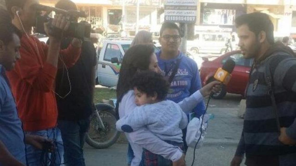 This picture of Lamia Hamdin holding her child as she interviewed people on a Cairo street sparked social media reactions. (Photo courtesy: Facebook)