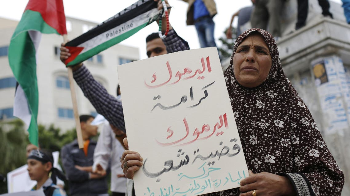 A Palestinian woman holds a placard during a gathering in Gaza City on April 9, 2015, in solidarity with the Palestinians living in Syria's Yarmuk refugee camp. (File: AFP)