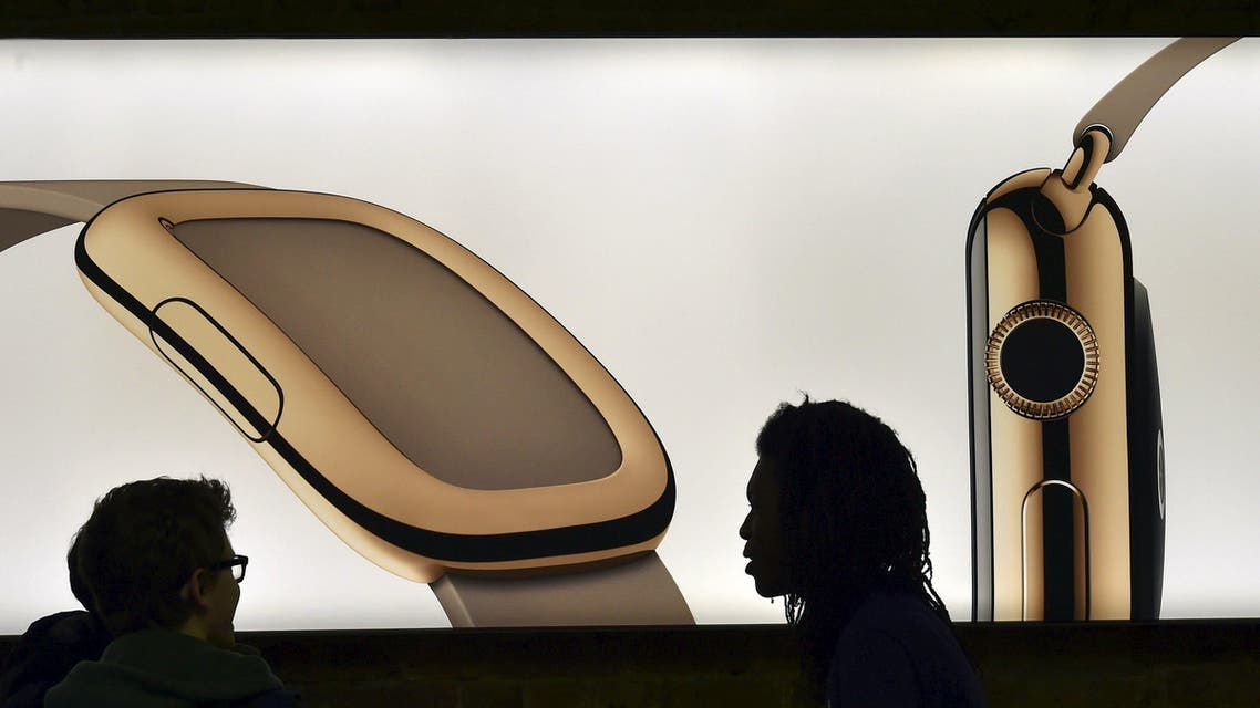 A customer and a staff member speak in front of a sample Apple Watch on a lightbox advertisement photograph at the Apple Store in London Reuters