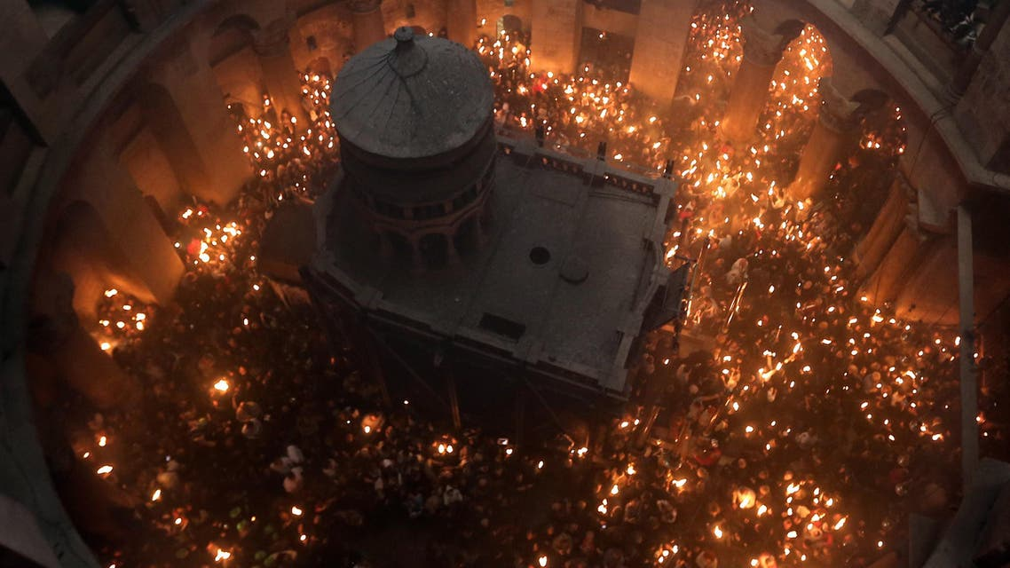 """Christian Orthodox worshipers hold up candles lit from the """"Holy Fire"""" as thousands gather in the Church of the Holy Sepulchre in Jerusalem's Old City, on April 11, 2015 during the Orthodox Easter ceremony of the """"Holy Fire"""". (AFP)"""