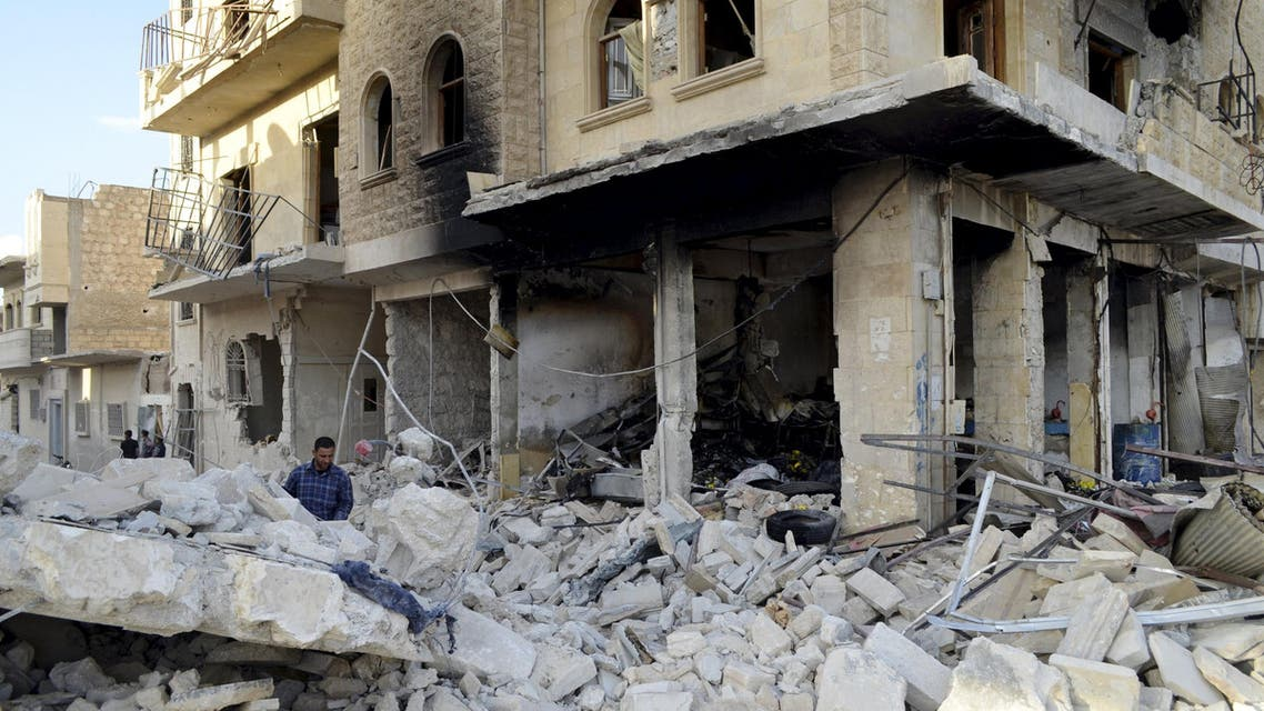Man inspects a site hit by what activists said were barrel bombs dropped by forces of Syria's President Bashar al-Assad, in Maaret al-Naaman town in Idlib province