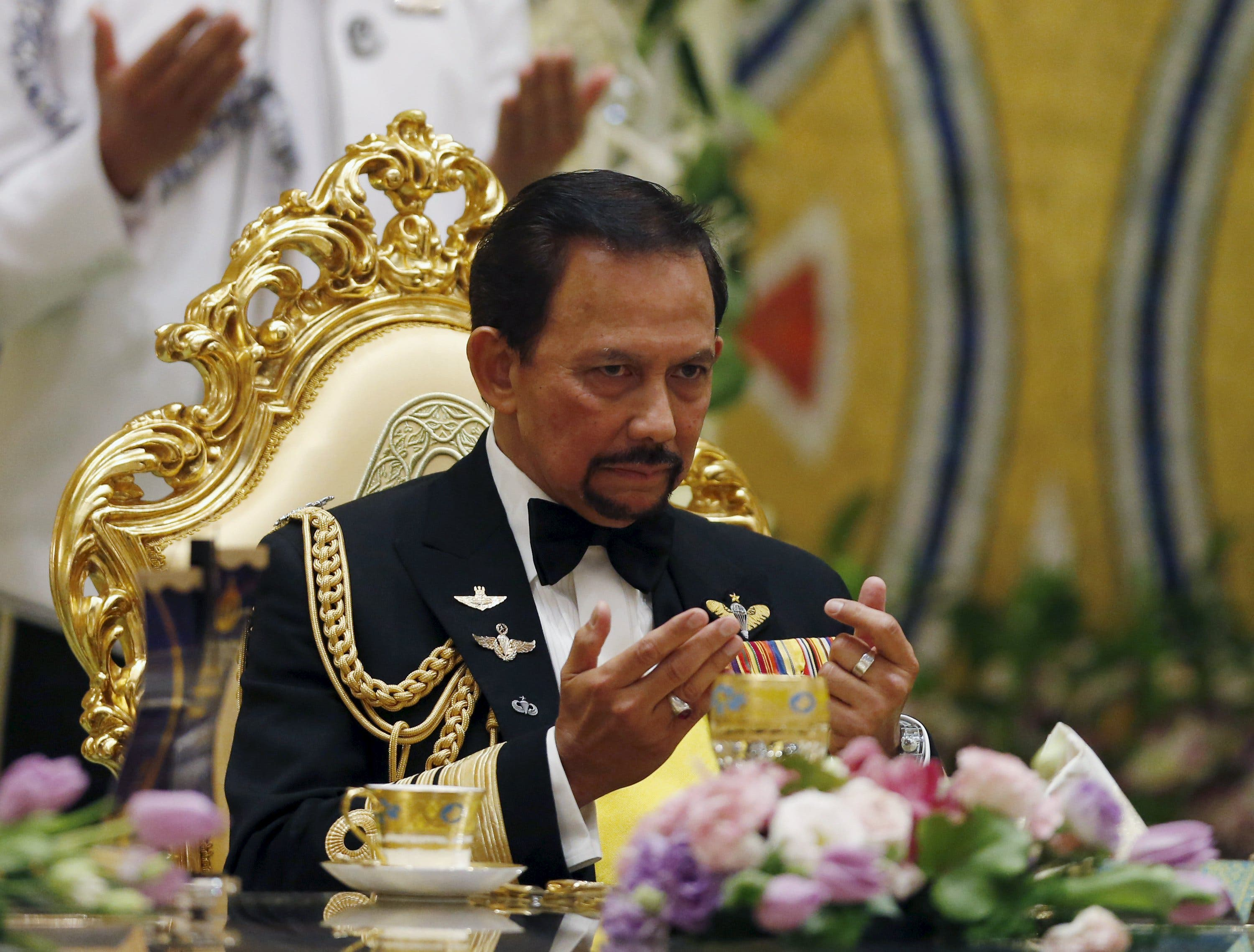 Brunei's Sultan Hassanal Bolkiah prays during the wedding banquet of the newly wed royal couple (Reuters)