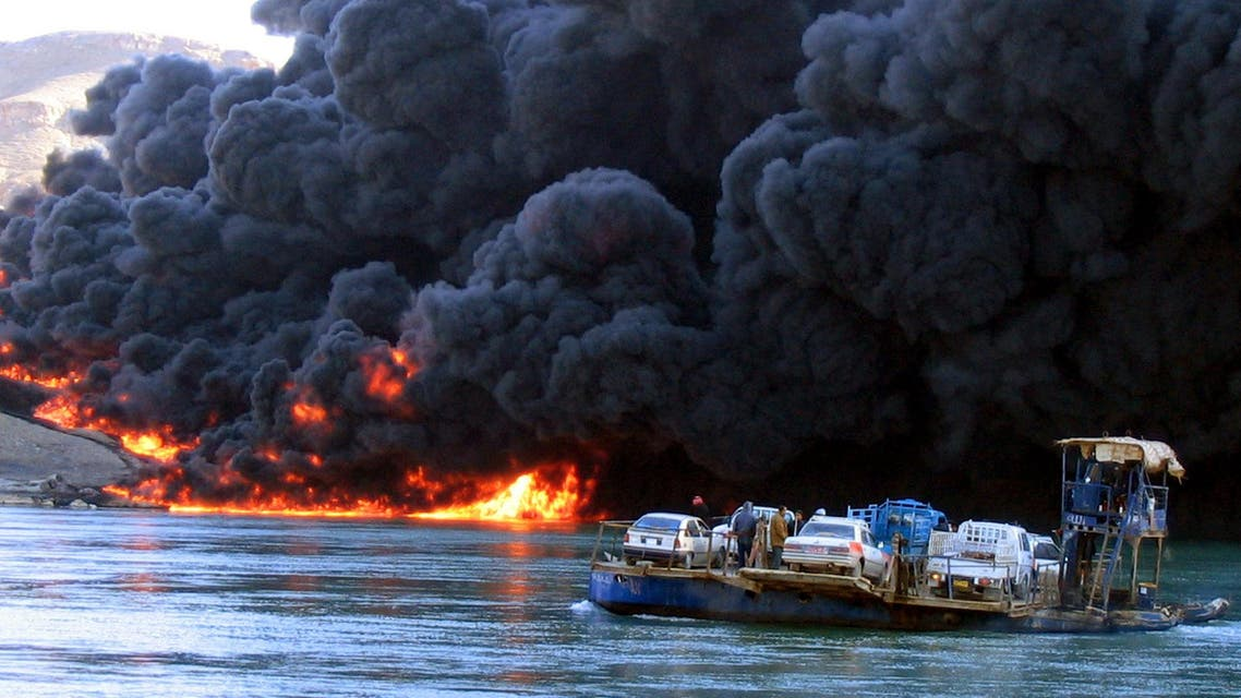A car ferry crosses the Tigris river outside Baiji, some 250 kilometers (150 miles) north of Baghdad Tuesday, Dec 21 2004 as an oil pipeline burns on the other bank. (