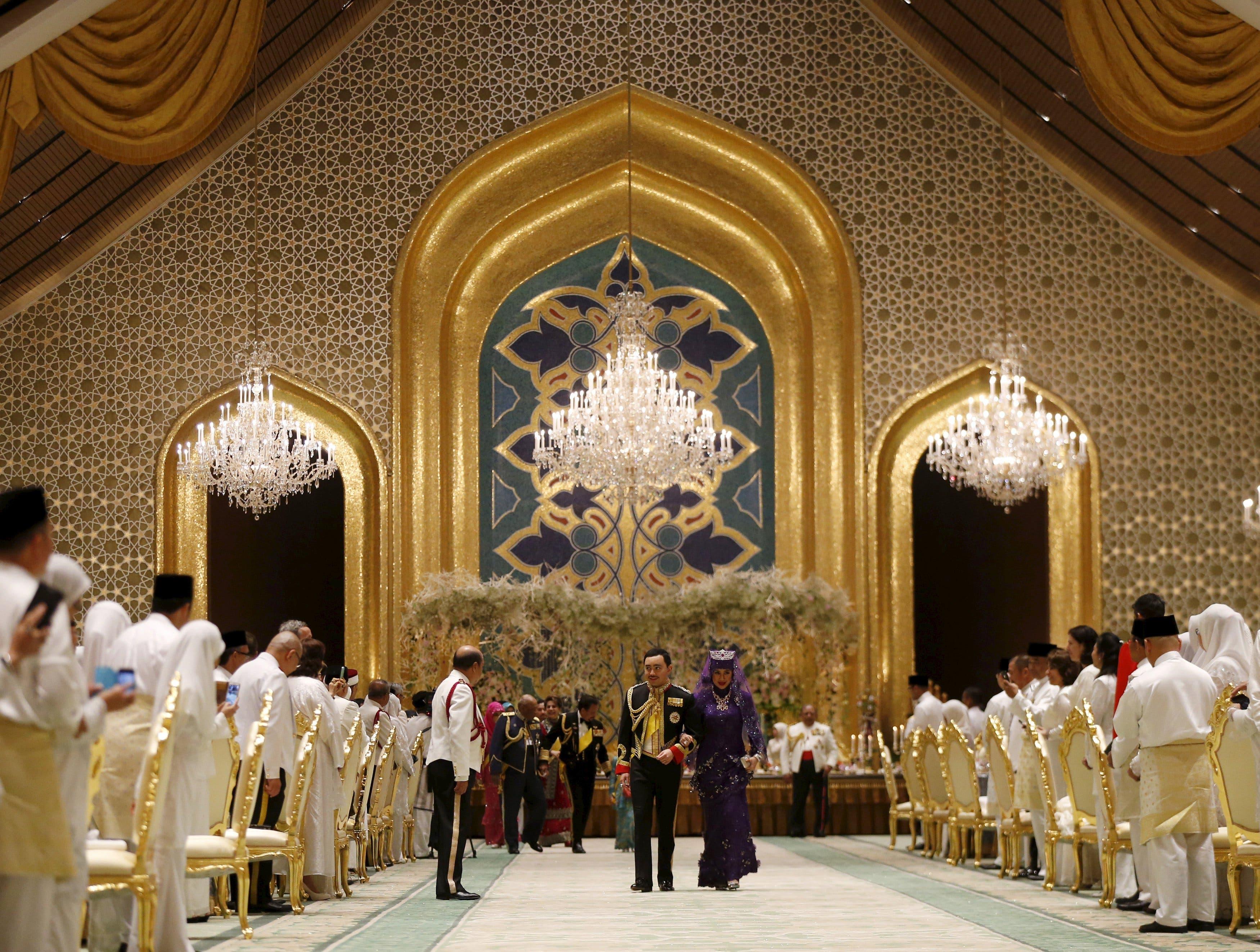 Brunei's newly wed royal couple, Prince Abdul Malik and Dayangku Raabi'atul 'Adawiyyah Pengiran Haji Bolkiah, leave the royal wedding banquet at the Nurul Iman Palace in Bandar Seri Begawan April 12, 2015. (Reuters)