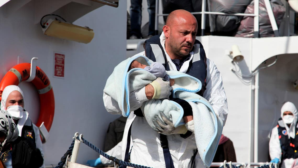 An officer carries a baby as migrants disembark from an Italian Coast Guard vessel after being rescued in Porto Empedocle, Sicily, southern Italy, Wednesday, March 4, 2015. AP