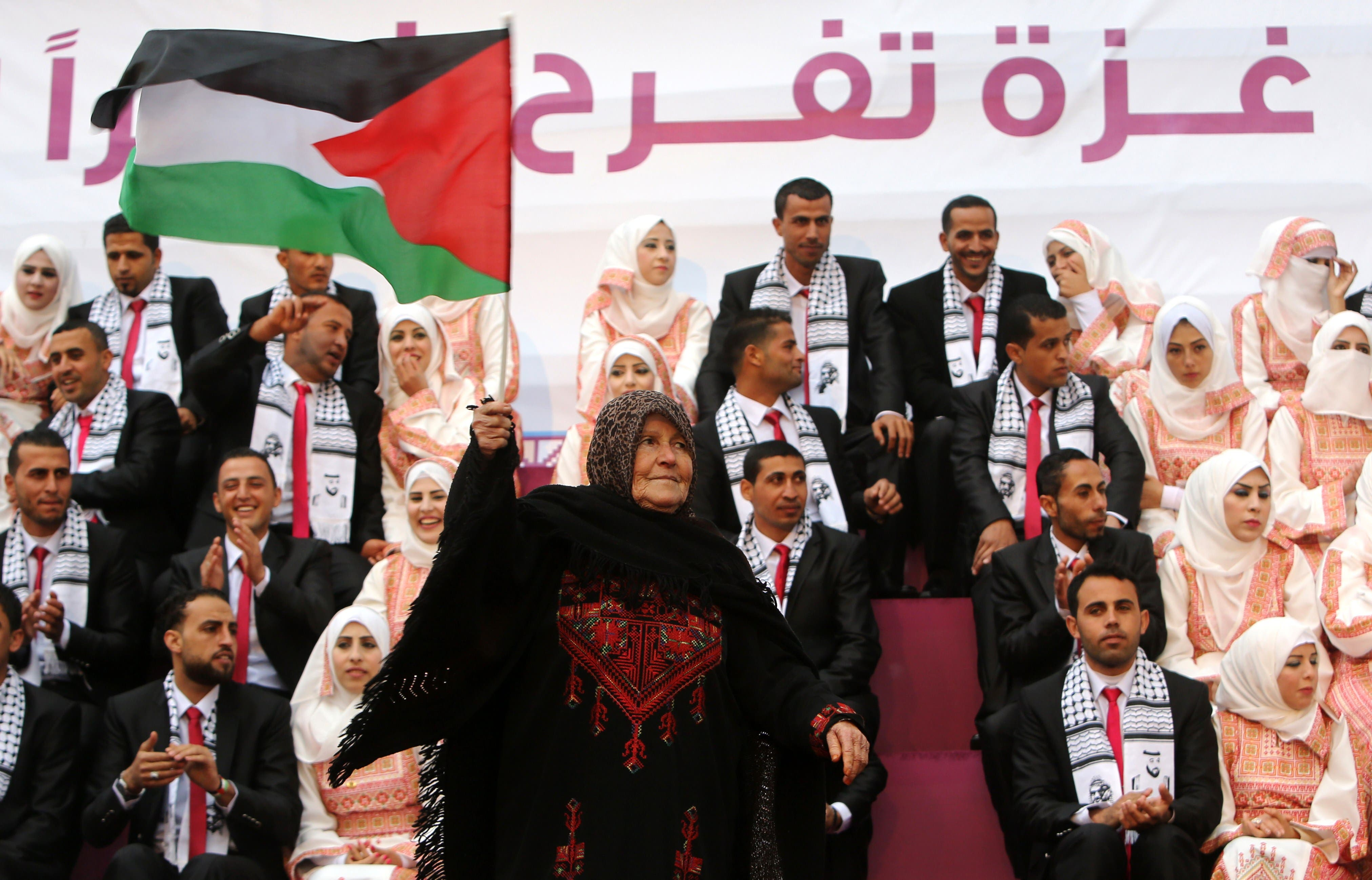 A Palestinian woman waves her national flag during a mass wedding ceremony in Gaza City, on April 11, 2015. AFP
