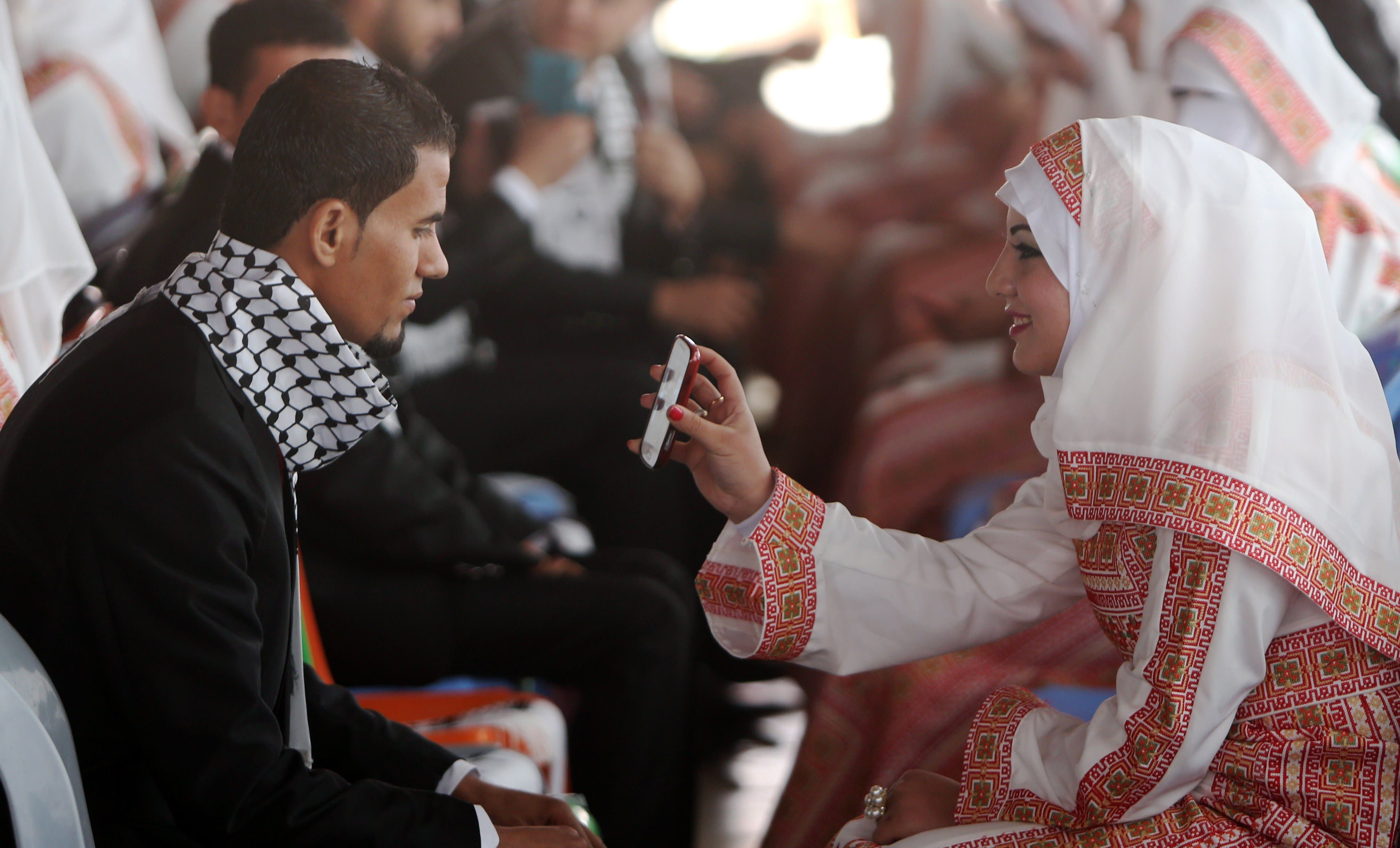 A Palestinian bride shows a phone-screen to her groom during a mass wedding ceremony in Gaza City, on April 11, 2015. (AFP)
