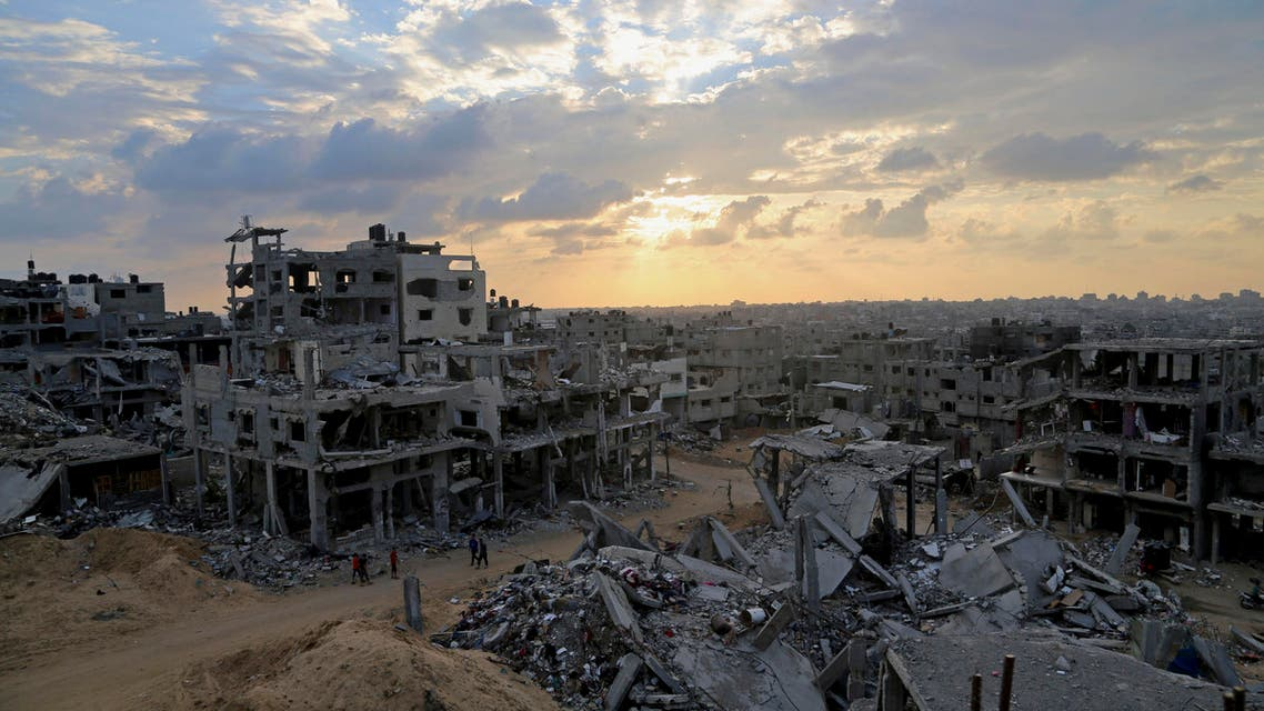 Palestinians walk during the sunset between the rubble of their destroyed building in Shijaiyah neighborhood of Gaza City in the northern Gaza Strip, Sunday, Oct. 12, 2014. (AP)