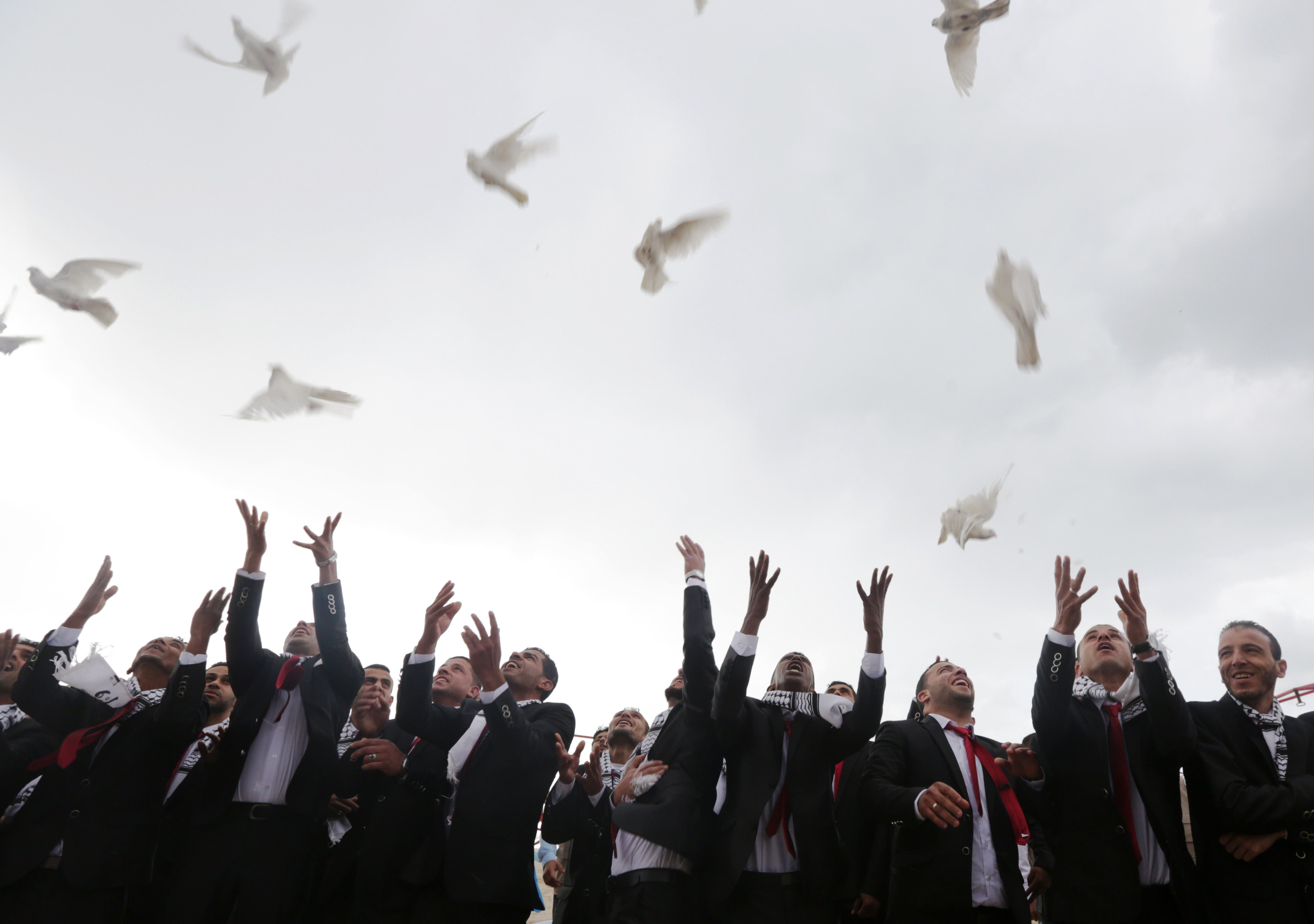 Palestinian grooms release doves during a mass wedding ceremony in Gaza City, on April 11, 2015. (AFP)