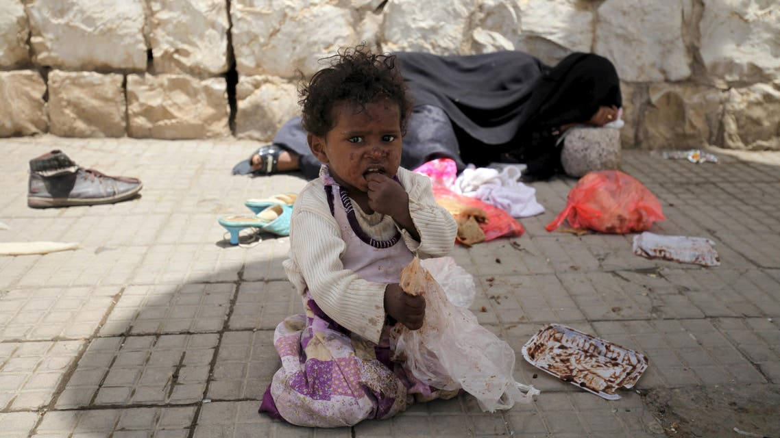 A girl sits in front of her mother sleeping on the sidewalk on a street in Sanaa Reuters