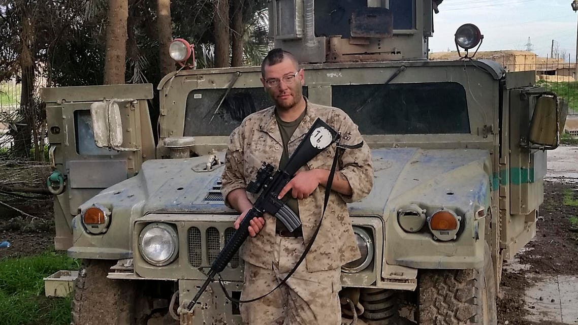 In this Feb. 26, 2015 photo, Jamie Lane, 29, an American veteran originally from Mt. Pleasant Michigan, poses for a picture in front of an Iraqi Army Humvee captured and later abandoned by Islamic State militants in Tel Hamis, Syria. Lane is among growing number of Iraq war veterans returning to the battlefield, this time without the American military, to join in the fight against the Sunni militants who now hold territory in a third of Iraq and Syria. (Courtesy Jamie Lane via AP)