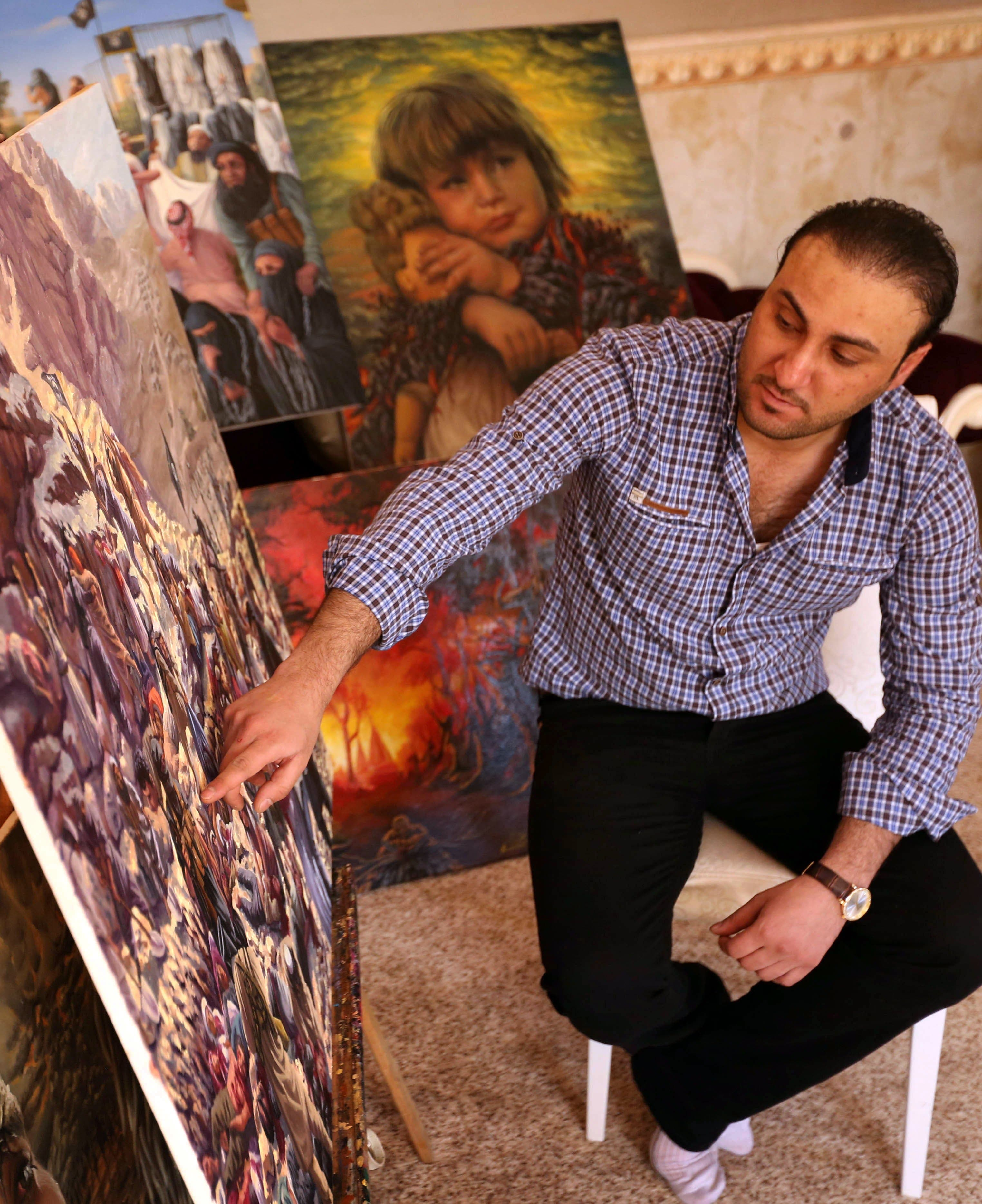 Iraqi painter Ammar Salim poses near some of his art pieces at his workshop in the Iraqi Kurdish city of Dohuk, on March 26, 2015. AFP