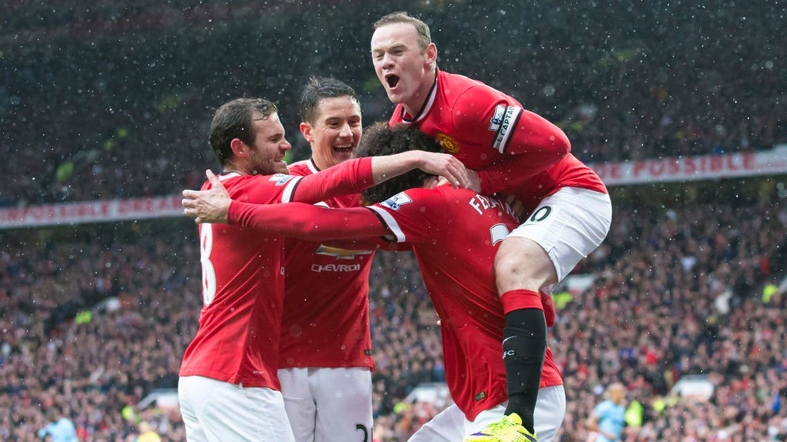 Manchester United's Marouane Fellaini, bottom right, celebrates with teammates including captain Wayne Rooney, top, after scoring during the English Premier League soccer match between Manchester United and Manchester City at Old Trafford Stadium, Manchester, England, Sunday, April 12, 2015. (AP Photo/Jon Super)