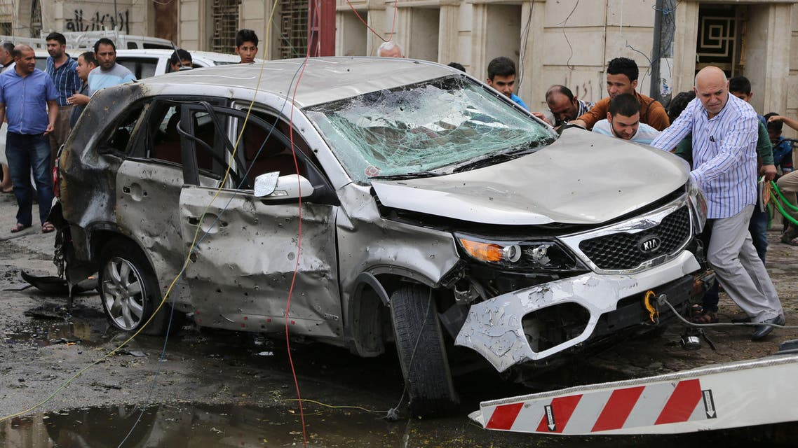 Iraqis try to lift a car at the site of a car bomb explosion at a convenience store in the Karrada neighborhood of Baghdad, Iraq, Friday, April 10, 2015. (AP)