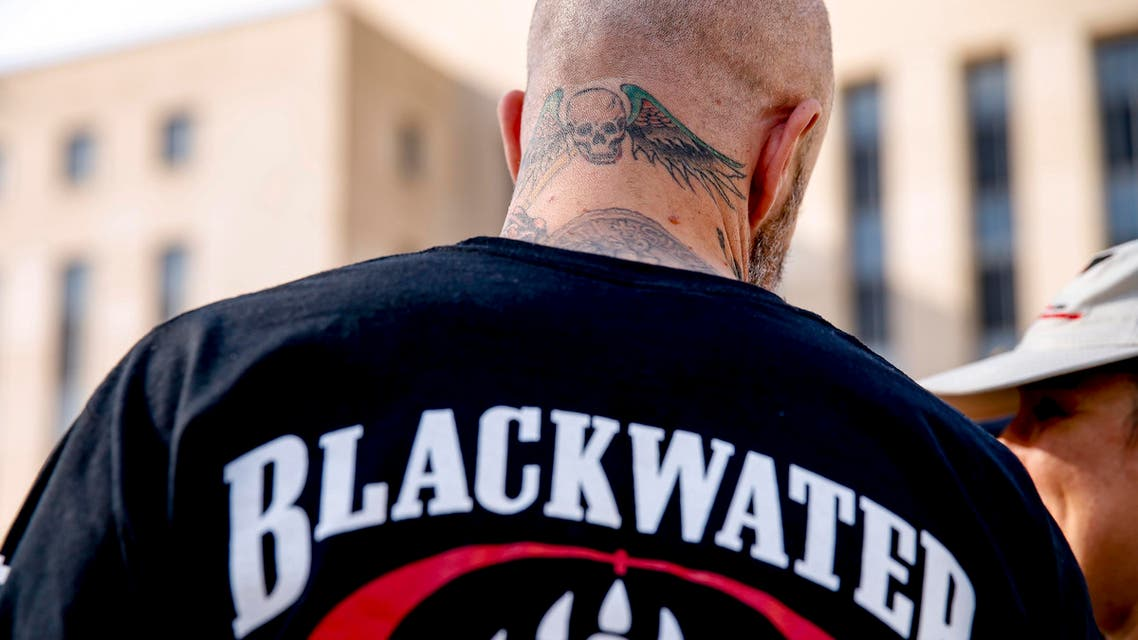 A former member of Blackwater joines family members, friends, and supporters of four former Blackwater security guards outside the federal court in Washington, Monday, April 13, 2015, following sentencing for four former Blackwater security guards in connection with a 2007 shooting of civilians in Iraq. U.S. District Judge Royce Lamberth sentenced Nicholas Slatten to life in prison while Paul Slough of Keller, Texas, Evan Liberty of Rochester, N.H., and Dustin Heard of Knoxville, Tenn., were convicted of manslaughter and received sentences of 30 years plus one day. (AP Photo/Andrew Harnik)