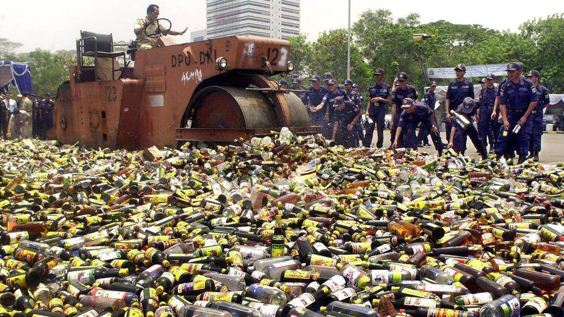 Government officials use a steamroller to destroy thousands of bottles of liquor and spirits confiscated from unlicensed stores in Jakarta, Indonesia. (File Photo: AP)