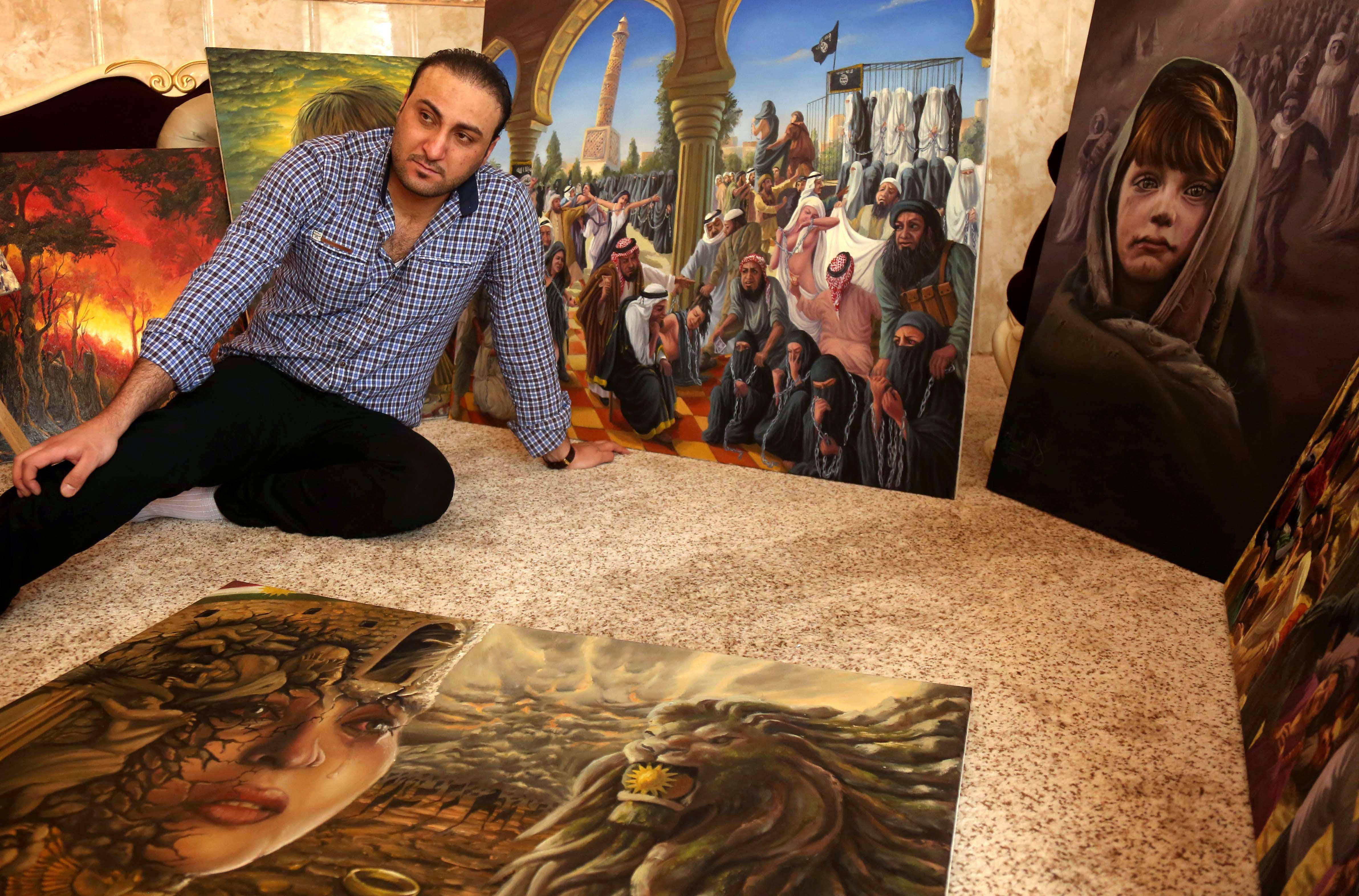Iraqi painter Ammar Salim poses near some of his art pieces at his workshop in the Iraqi Kurdish city of Dohuk, on March 26, 2015. (AFP)