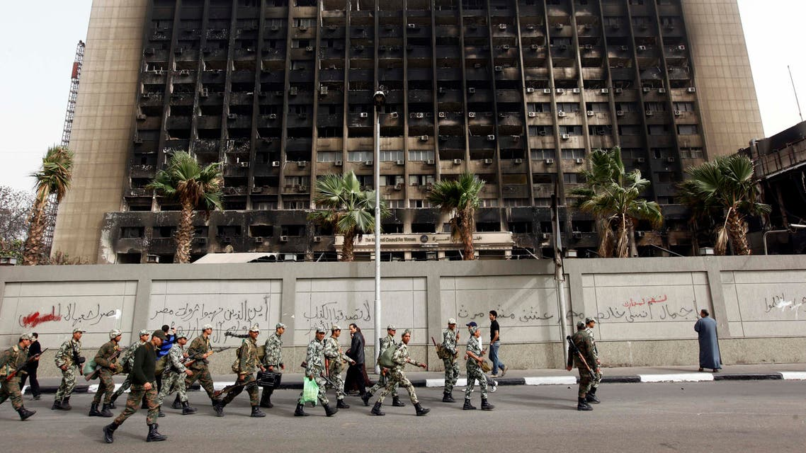 Army soldiers march in front of the burned down building of Hosni Mubarak's National Democratic Party in Cairo. (File: AP)
