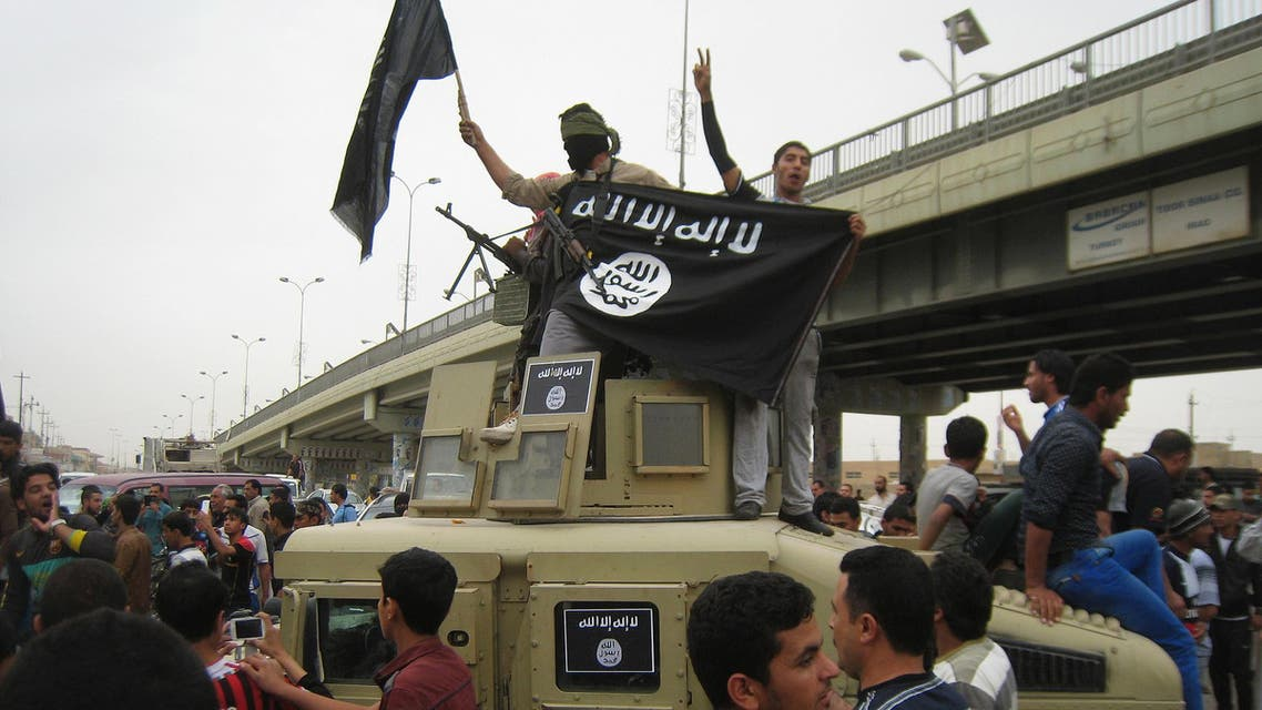 In this Sunday, March 30, 2014, file photo, Islamic State group militants hold up their flag as they patrol in a commandeered Iraqi military vehicle in Fallujah, 40 miles west of Baghdad, Iraq. (AP)