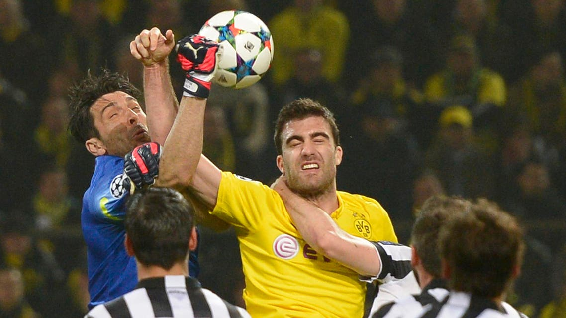 Juventus goalkeeper Gianluigi Buffon, left, and Dortmund's Sokratis Papastathopoulos challenge for the ball during the Champions League round of 16 second leg soccer match between Borussia Dortmund and Juventus Turin on Wednesday, March 18, 2015 in Dortmund, Germany. (AP Photo/Martin Meissner)