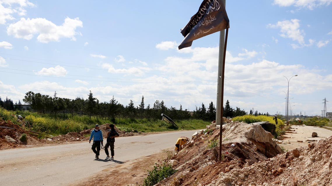 Members of al Qaeda's Nusra Front walk near the Nusra flag as it flutters at a checkpoint at the entrance of Idlib city, April 14, 2015.  Reuters