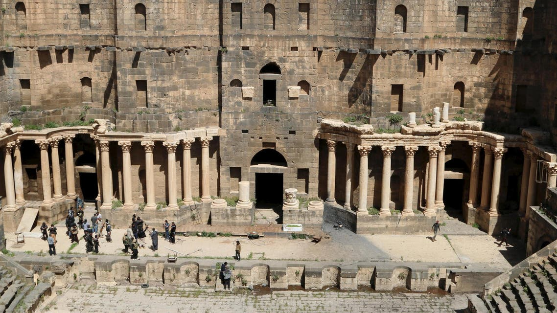 Rebel fighters walk inside a 2nd century Roman amphitheater in the historic Syrian southern town of Bosra al-Sham, after they took control of the area March 25, 2015. Reuters