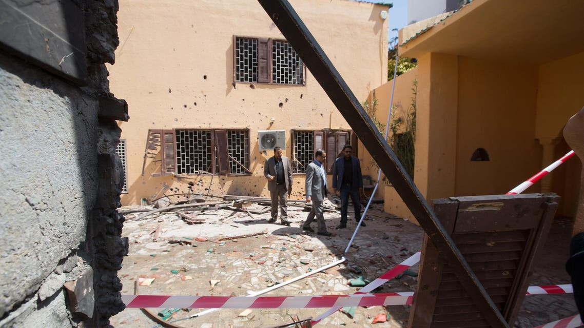 Officials survey the grounds of the the Moroccan Embassy in Tripoli, Libya after a bomb left in a garbage bin exploded on Monday, April 13, 2015. (AP)