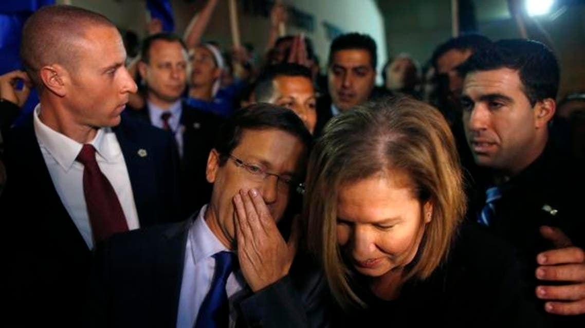 Isaac Herzog (L) speaks with Tzipi Livni, his co-leader of the center-left Zionist Union party, while campaigning outside a polling station in Modiin near Tel Aviv March 17, 2015. (AP)