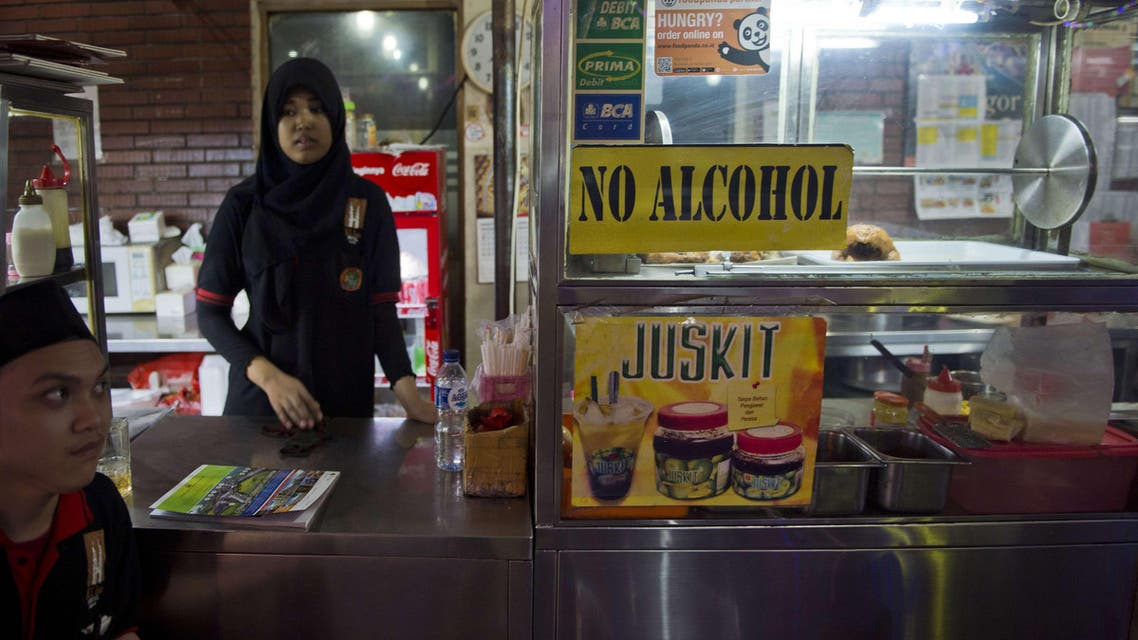 An Indonesia restaurant worker waits for customers as a no alcohol sign is displayed on the food stall in a tourist district in Jakarta. (AFP)