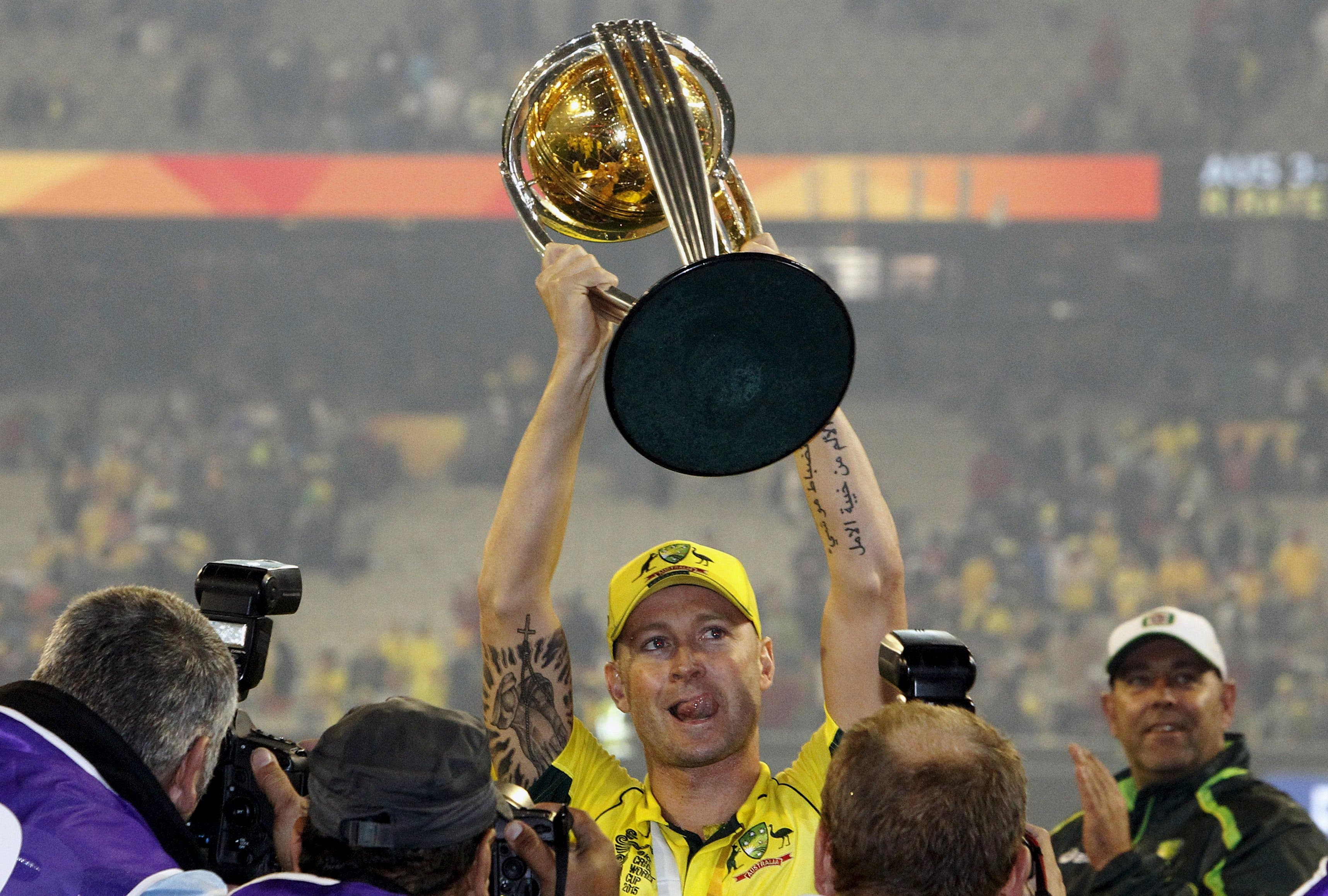 Australia's captain Michael Clarke (C) holds the Cricket World Cup trophy as he celebrates after they defeated New Zealand in the final match at the Melbourne Cricket Ground (MCG) March 29, 2015. REUTERS/Brandon Malone