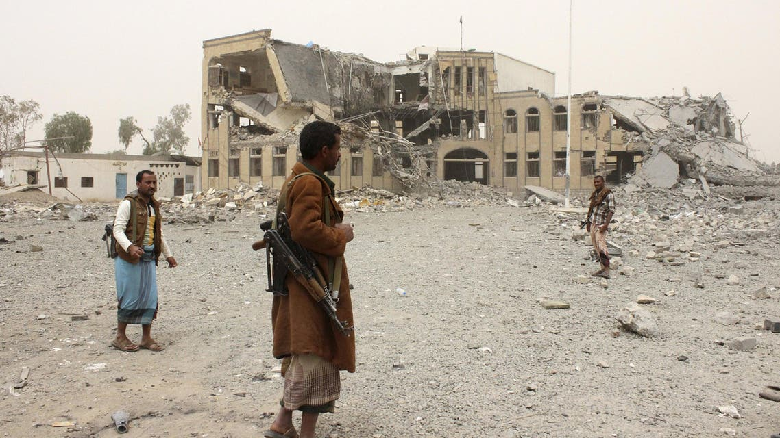 Police troopers stand near the building of police headquarters, destroyed by Saudi-led air strikes, in Yemen's northwestern city of Saada. (Reuters)