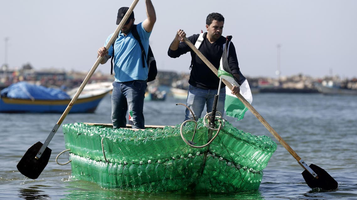 Palestinian Baha Abed (L) and his cousin Mohamed Abed paddle on their makeshift boat made of plastic bottles on April 18, 2015 at the port of Gaza City. (AFP)