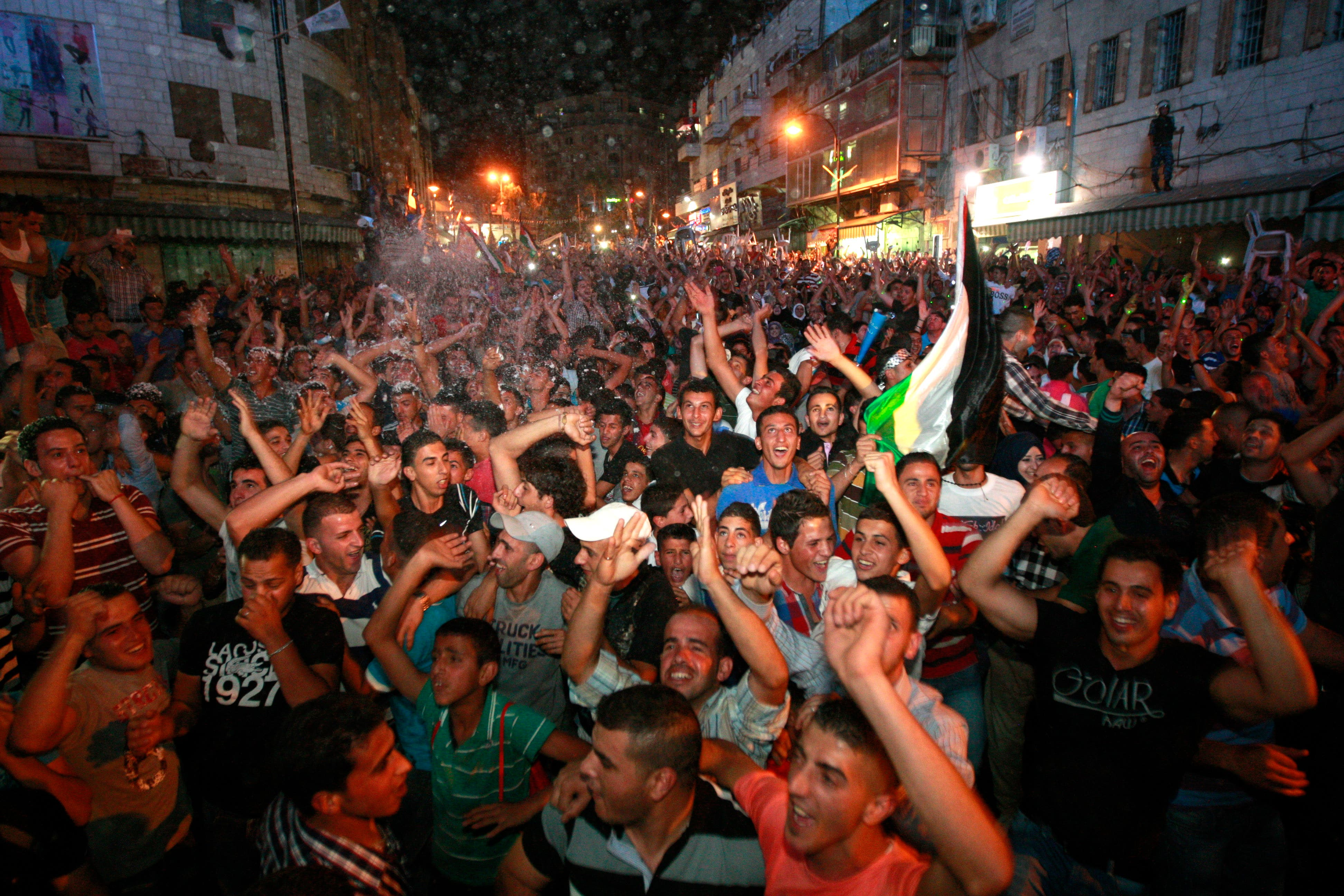 Palestinians celebrate after Palestinian singer Mohammed Assaf won a regional TV singing contest, in the West Bank city of Ramallah, Saturday, June 22, 2013. (AP)