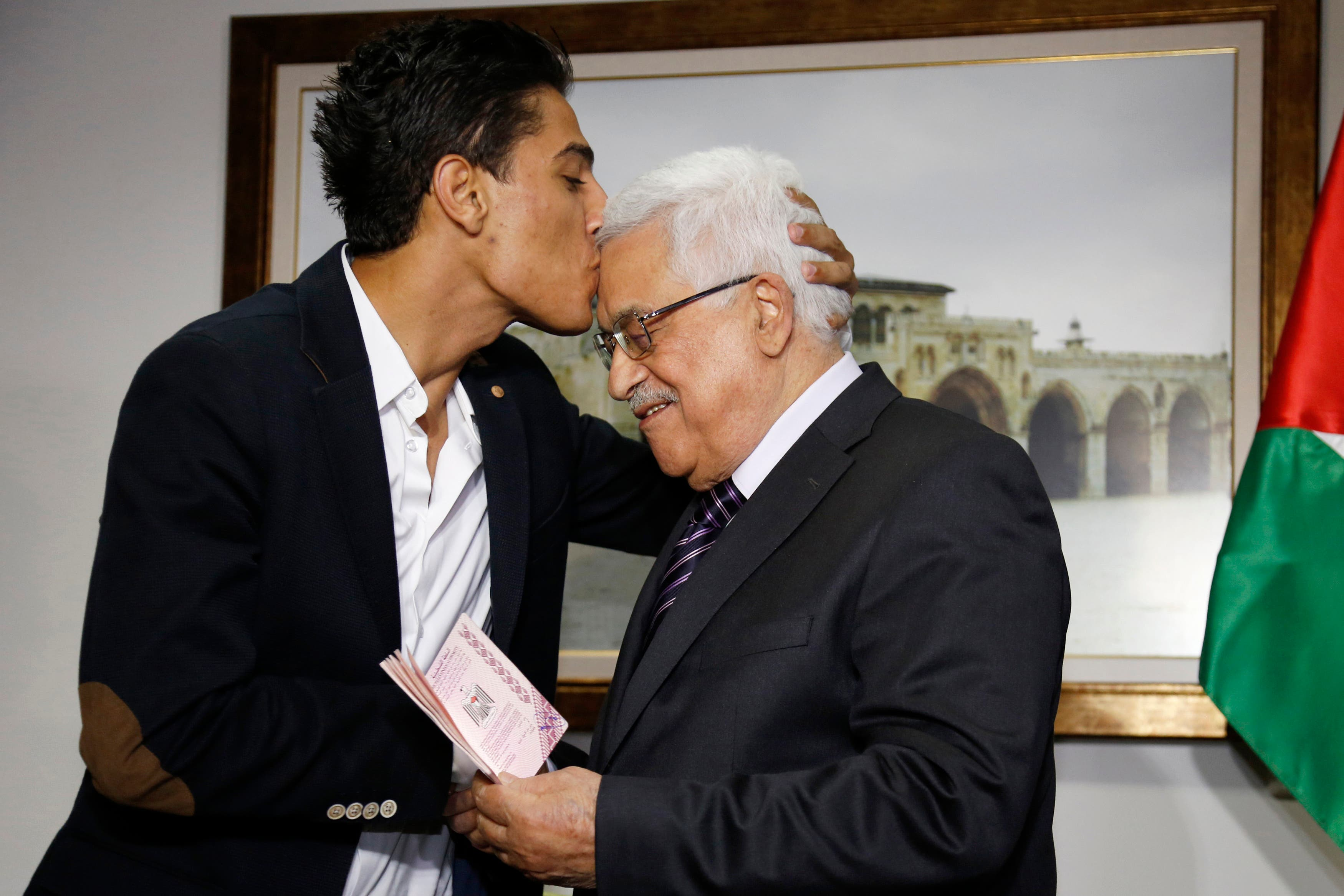 Arab Idol Mohammed Assaf, left, kisses Palestinian President Mahmoud Abbas as he hands him a diplomatic Palestinian Authority passport during their meeting in the West Bank city of Ramallah, Monday, July 1, 2013.  (AP)