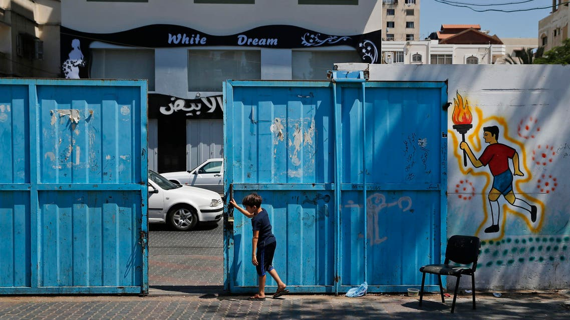 A Palestinian boys closes the gate of a United Nations school where hundreds of families sought refuge after fled their homes due to heavy Israeli missile strikes in Gaza City, Wednesday, July 23, 2014. (AP)