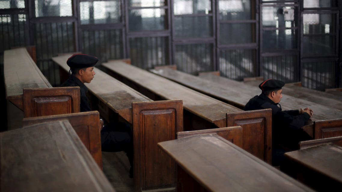 Policemen sit in front of empty bars during the trial of Muslim brotherhood leaders in Cairo, April 11, 2015. (AP)
